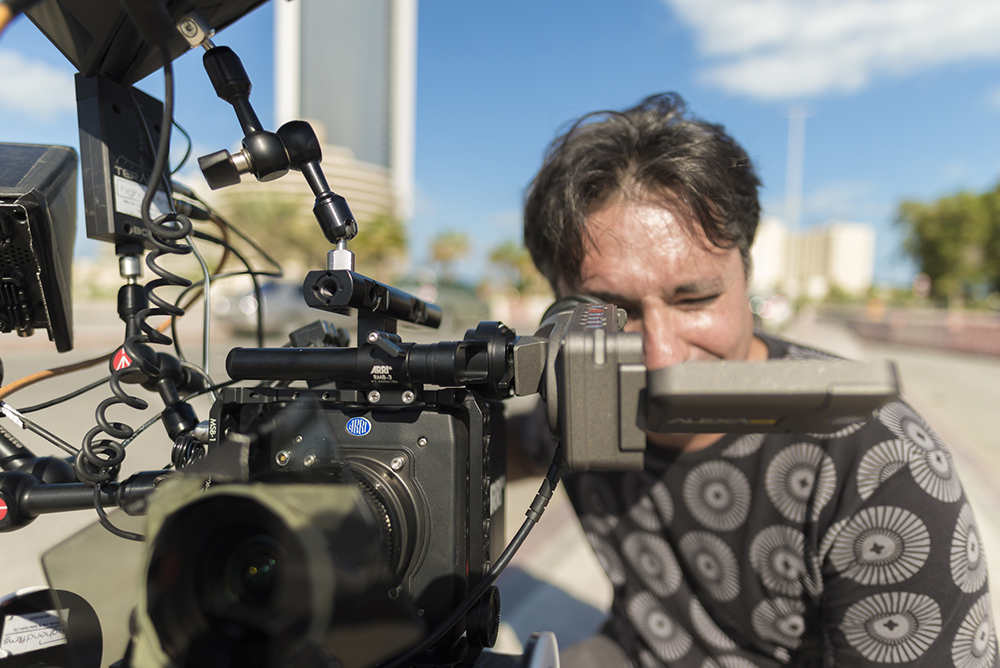 This is a landscape picture of Matteo Curcio looking through the scope of a fully rigged Arri Alexa Mini in Abu Dhabi, UAE.